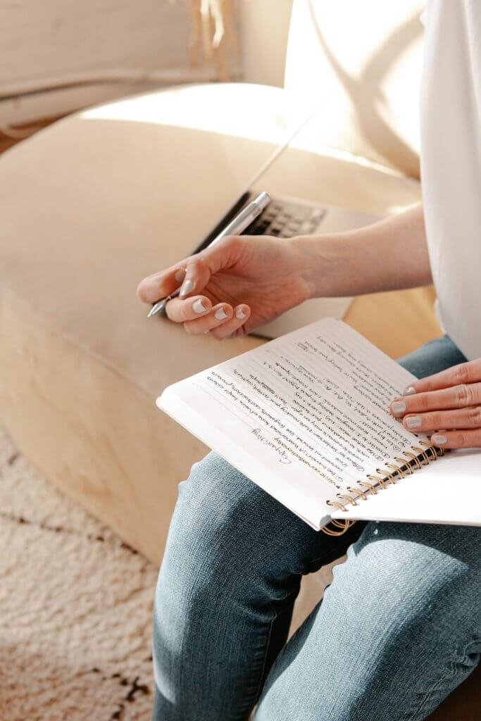 person in white shirt and blue denim jeans holding white book and writing